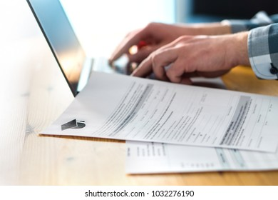 Young man writing college or university application form with laptop. Student applying to school. Scholarship document, admission paper or letter on table. Typing email. Education and communication.