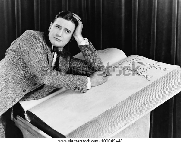 Young man writing into an oversized note book