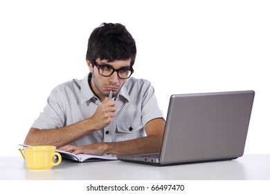 young man writing and looking to his laptop computer