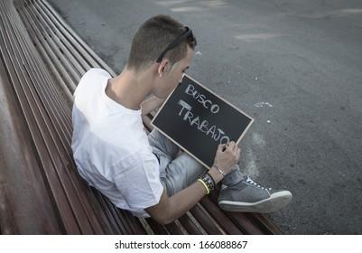 Young man writing I need job in spanish on a blackboard
