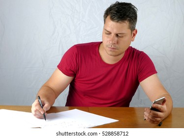 Young man writing on a paper and holds smart phone in his hand