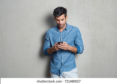 Young man writing phone message. Mid adult man typing on mobile while standing on grey background. Latin man leaning on gray wall while browsing internet on smartphone.