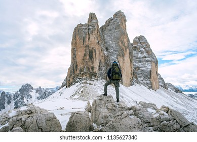 young man wyth knapsack hiking in dolomiti alps mountain