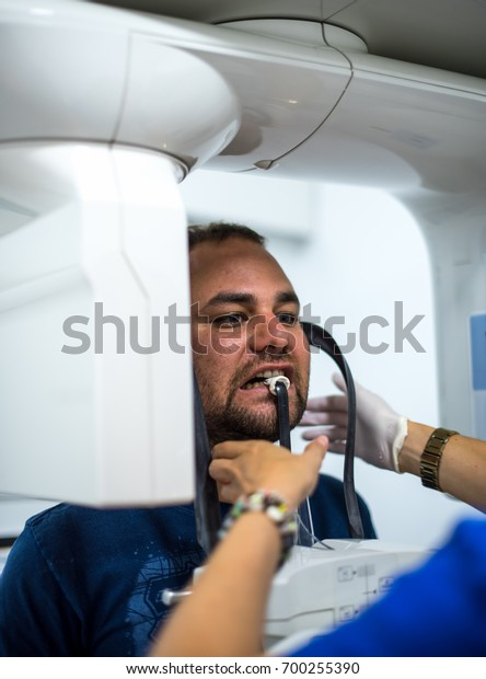 Young man at x ray machine in dentist clinic