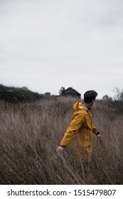 young man in a yellow raincoat in a field. happy young man wearing yellow raincoat standing in a wheat field. shows emotions. cheerful man in windy foggy mountain.