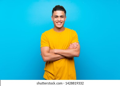 Young man with yellow shirt over isolated blue background keeping the arms crossed in frontal position