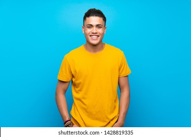 Young man with yellow shirt over isolated blue background laughing