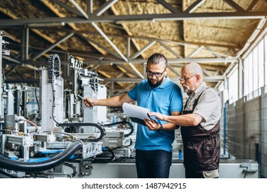 Young manager with beard showing and inspecting working process of adult professional worker on the big factory