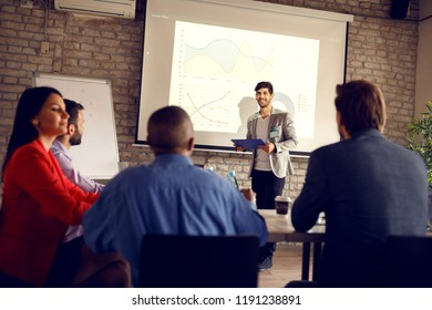 Young manager in company holding lecture to business group