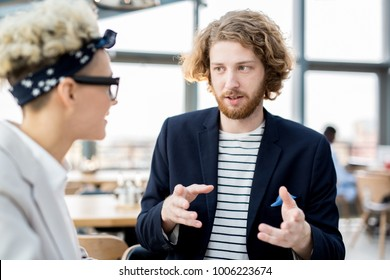 Young manager explaining his viewpoint to colleague during start-up meeting
