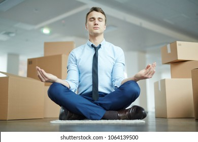 Young manager in formalwear sitting on the floor in pose of lotus and meditating after stressful day in new office