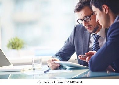 Young manager listening to his colleague explanations