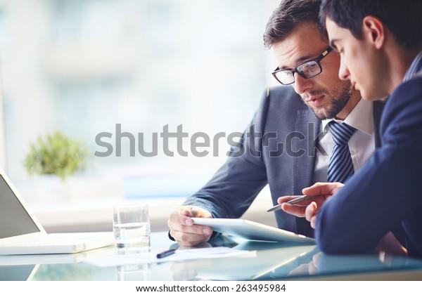 Young Manager hört Erklärungen seines Kollegen an