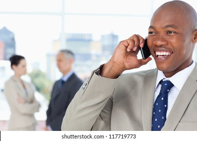 Young manager looking towards the side while laughing and talking on the phone