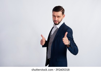 Young manager showing Like. Studio photo of the young guy in a suit.