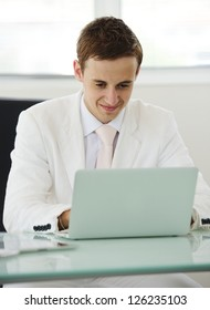 Young manager sitting at desk in bright office, working on laptop