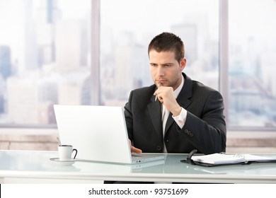 Young manager sitting at desk in bright office, working on laptop.?