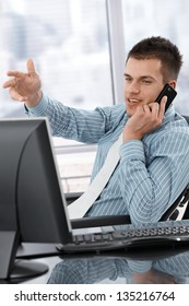 Young manager sitting at desk, using mobile phone, working