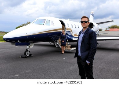 Young manager standing by the executive jet waiting with the flight attendant