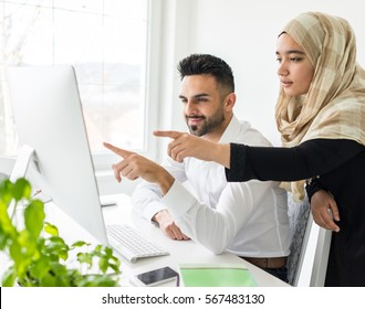 Young mand and woman working in office on computer