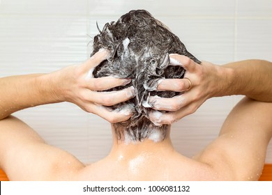 young manis washing his hair, taking a shower with foam on his head holds fingers in hair in bathroom, he use shampoo, attractive young guy is cleaning his body, health care concept