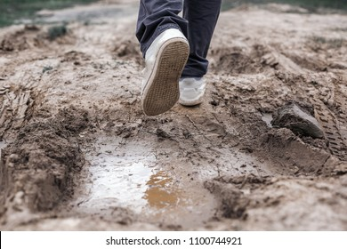 The young man's feet are crossing the muddy road to reach the destination waiting for him in the foreground.