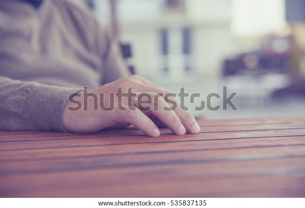 young man's hand with a gold wedding ring on  wooden table, blurred background