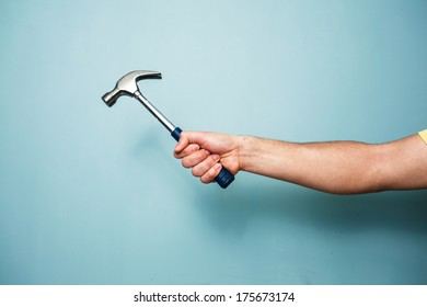 A young man's hand is holding a hammer against a blue wall