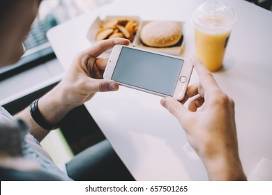 Young man's hand holding mobile phone. Cute guy is sitting in an elegant cafe. He is scrolling and reading some stuff. Place for your advertisment or logo. Close up. Horizontal position of the phone