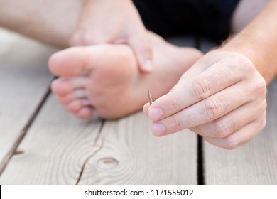 Young man's hand showing wooden splinter after removing it from foot. Accident on wooden floor after walking by barefoot. Front view. Close up.