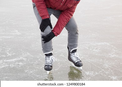Young man's hands in gloves touching his knee during ice skating time in winter day. Pain after falling on frozen lake. Sporty problem and solution. Front view.