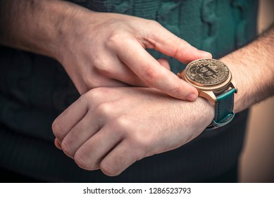 Young man's hands setting watch with a bitcoin golden penny, time to act concept