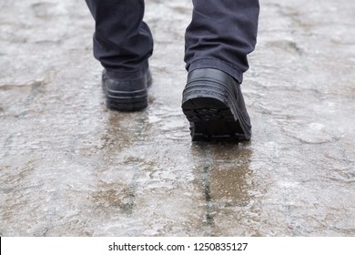 Young man's legs in black leather boots walking on sidewalk in wet, warm winter day. Pavement covered with slippery ice. Closeup. Back view.
