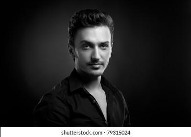 Young man's portrait. Close-up face against black background