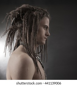 Young man's portrait. Stylish handsome sexy Guy with Dreadlocks and ethnic Jewelry, Accessories (necklace, bracelet, ring) Close-up face. Tribal Style. Trendy youthful man's look
