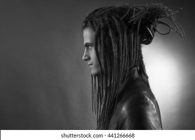 Young man's portrait. Stylish handsome sexy Guy with Dreadlocks in black leather fashionable jacket, Close-up face. Tribal Style. Trendy youthful man's look