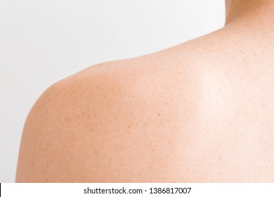 Young man's skin with brown freckles on shoulder. Isolated on light gray background. Back view. Closeup.