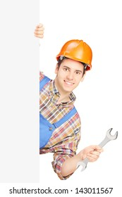 Young manual worker with helmet holding a wrench and posing behind a blank panel isolated on white background