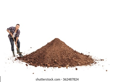 Young manual worker shoveling a pile of dirt and looking at the camera isolated on white background