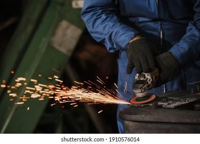 Young manual worker using grinder on metal in factory. Worker grinding in a workshop. Heavy industry factory, metalwork