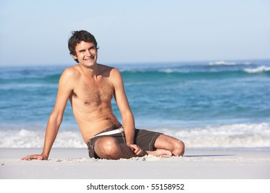 Young ManWearing Swimwear Sitting On Sandy Beach