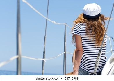 Young marine style woman is sitting on the boat and looking forward