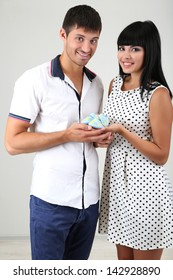 Young married couple with baby clothes on grey background