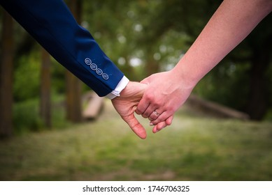Young married couple, bride and groom, holding hands on the wedding day. Wedding theme with blurred green background.