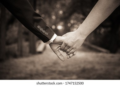 Young married couple, bride and groom, holding hands on the wedding day. Wedding theme with sepia filter. Shallow DOF. Selective focus