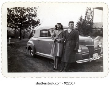 Young married couple circa 1943 with car.Organic fading and artifacts.