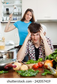 Young married couple having quarrel at home kitchen