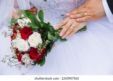 young married couple holding hands with beautiful flower bouquet focus on hands