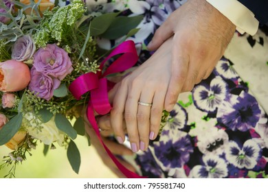 young married couple holding hands with beautiful flower bouquet