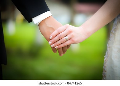 Young married couple holding hands, ceremony wedding day